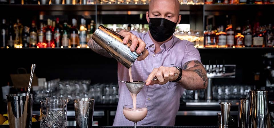 Bartender straining a mixed pink drink into a stem glass.