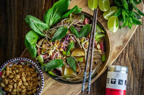 Bowl of Vietnamese noodles with basil on top and limes on the side.
