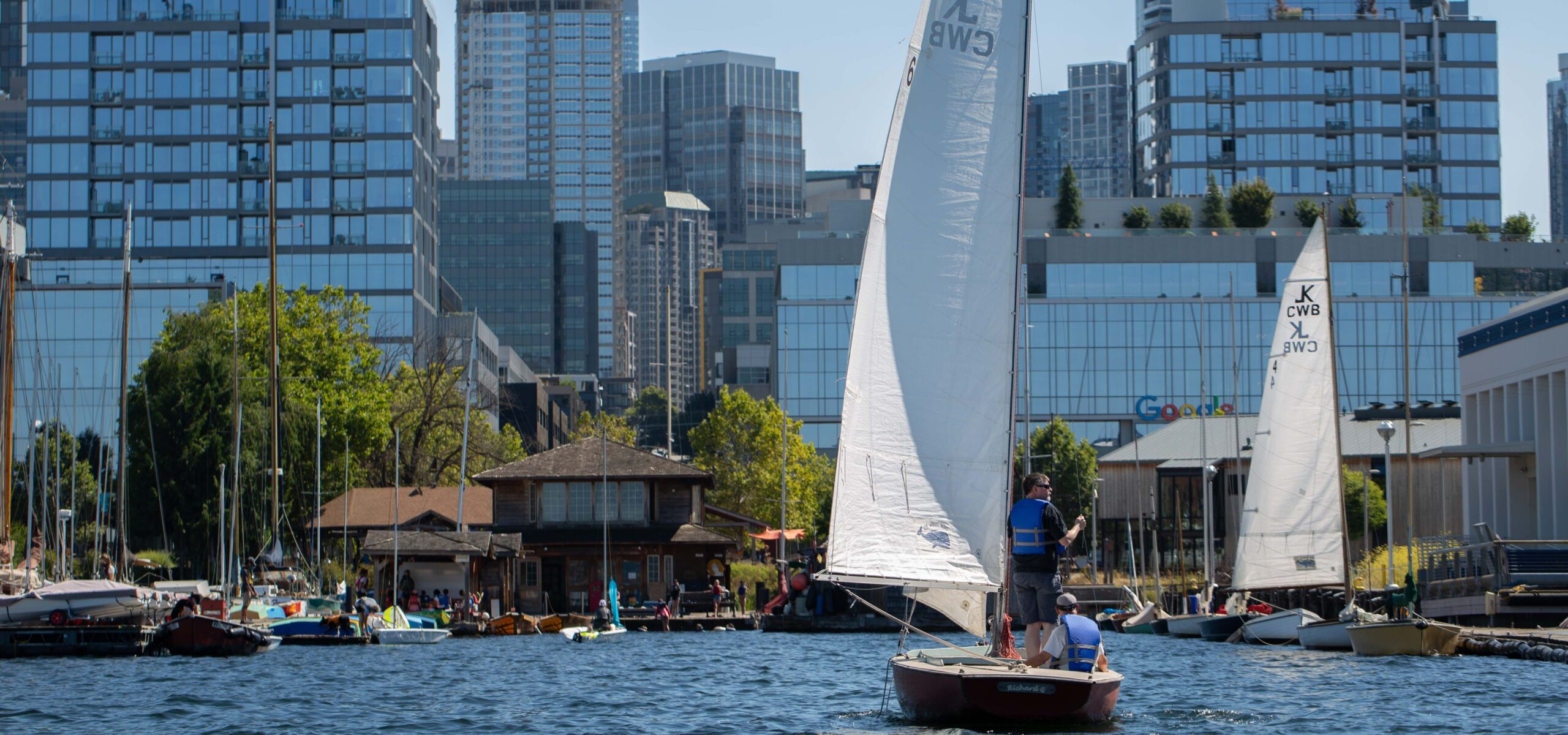 Two people on a sailboat on Lake Union with downtown Seattle in the background.
