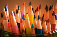 Color pencils pointing up from a cup they've been place in.