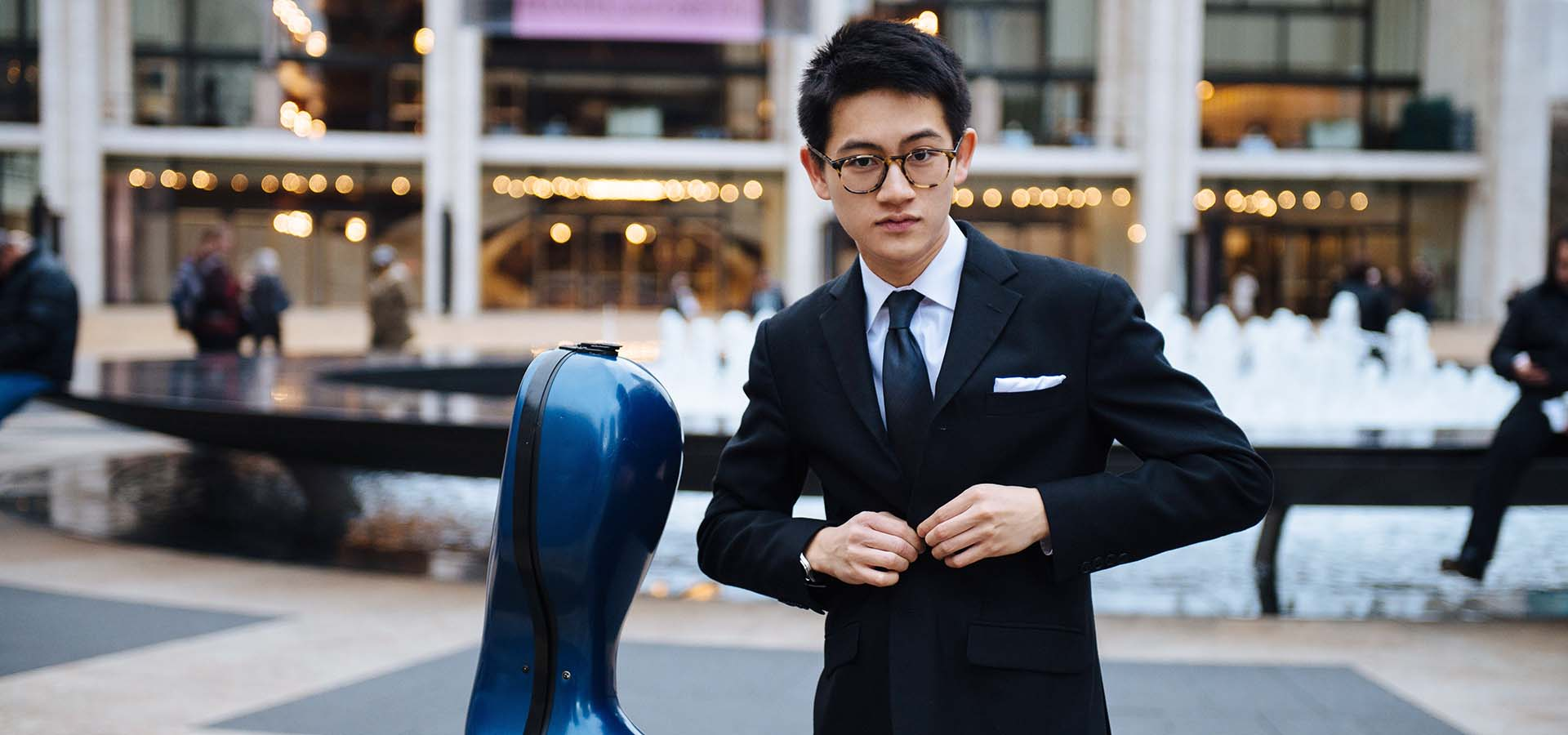 Asian cellist buttoning his coat