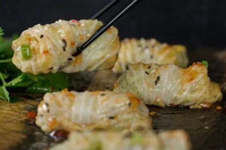 Chicken cabbage dumplings with sweet chili sauce drizzled on top.