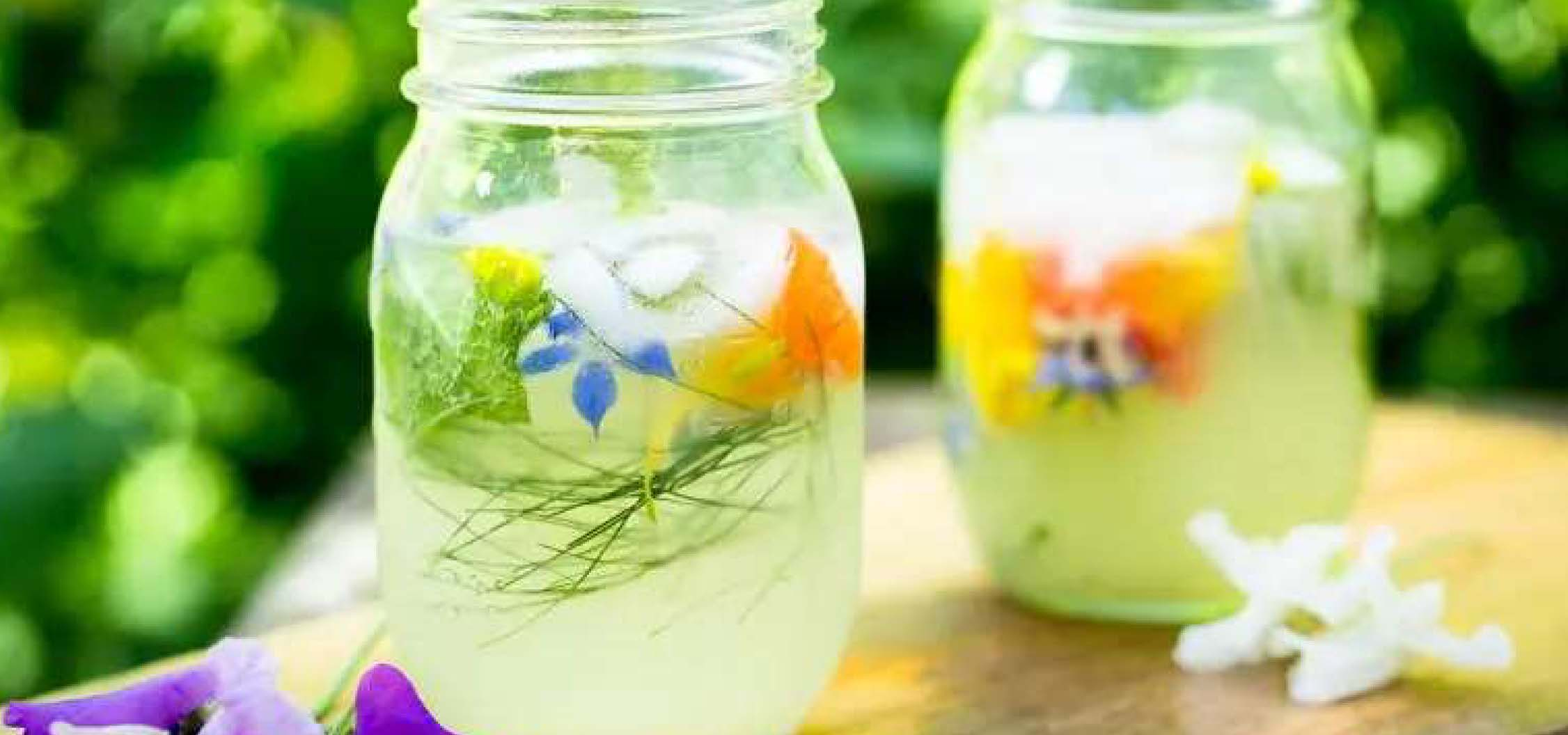 Two drinks mixed in mason jars, garnished with spring flowers.