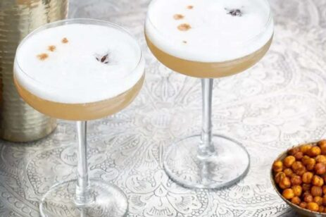 Two cocktail glasses with spiced gin drinks and a side of spiced nuts.