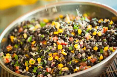 Colorful black bean salad being tossed in a metal bowl.