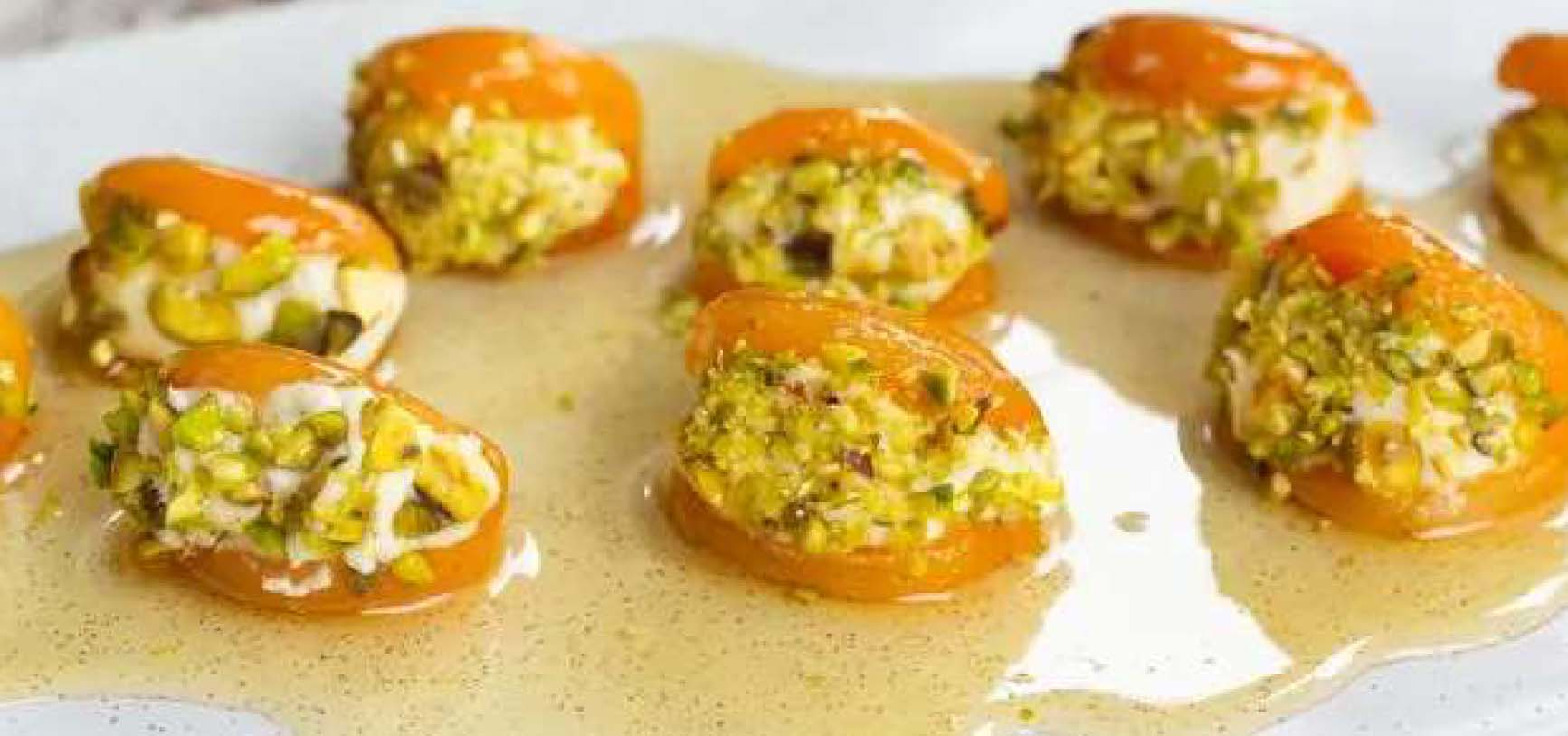 Apricots stuffed with cheese and pistachios, drizzled with honey on a platter.