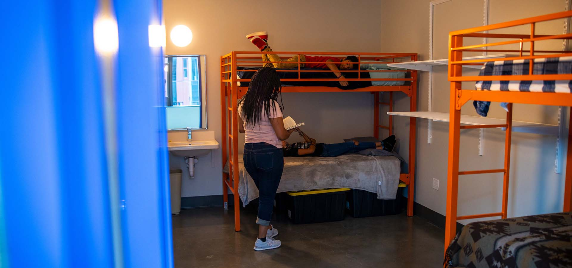 Volunteer shelter worker speaking with kids on a bunk bed.