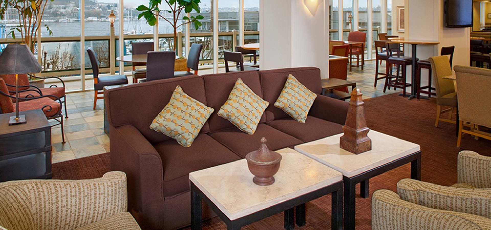 Inside of a hotel lobby with seating areas.