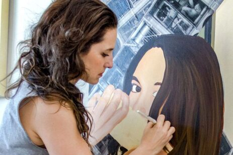 Woman painting another portrait of a woman.